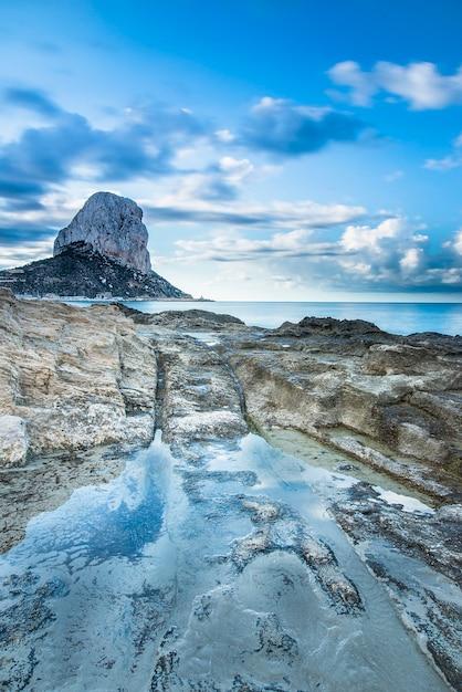 Paisagem costeira, com rochas em primeiro plano e a rocha ifach no horizonte Foto Premium