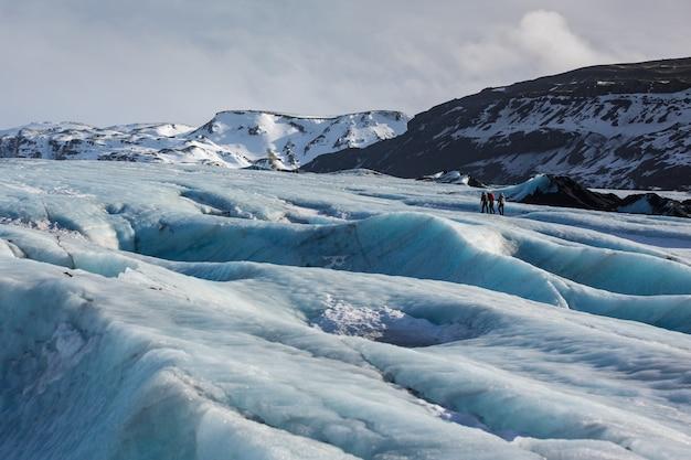 Paisagem da geleira com guia particular e casal de caminhante à distância, Foto Premium