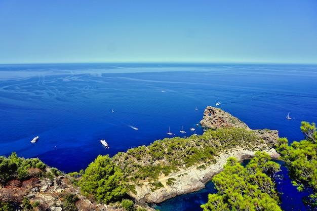Paisagem da ilha de sa foradada mallorca, espanha dos penhascos. barcos avistam o mar azul. Foto Premium