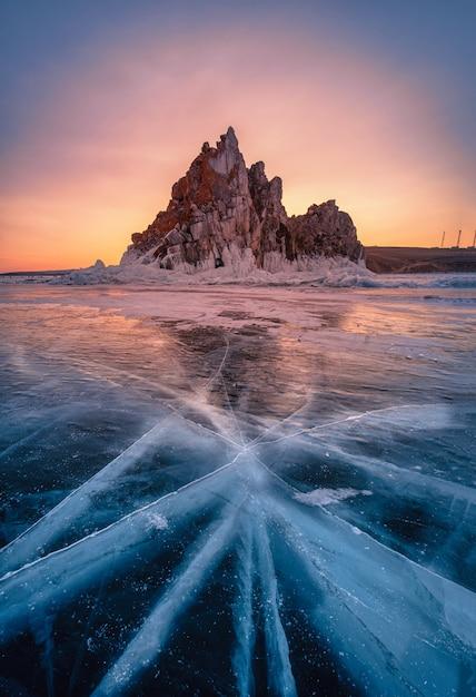 Paisagem da rocha de shamanka no nascer do sol com gelo de quebra natural na água congelada no lago baikal, sibéria, rússia. Foto Premium