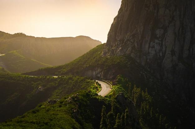 Paisagem das montanhas cobertas de vegetação com estradas nelas sob um céu nublado durante o pôr do sol Foto gratuita