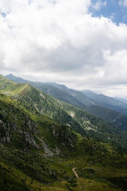 Paisagem de colinas cobertas de vegetação com montanhas rochosas sob um céu nublado Foto gratuita