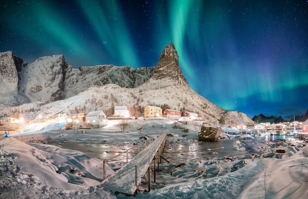 Paisagem de montanha de neve com aurora boreal na aldeia escandinava Foto Premium