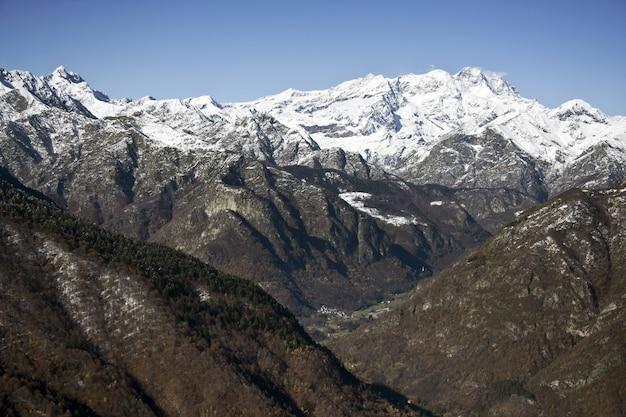 Paisagem de montanhas cobertas de árvores e neve sob a luz do sol e um céu azul Foto gratuita