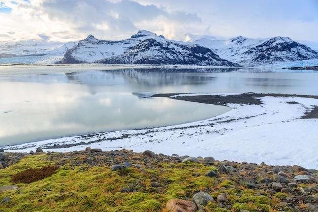Paisagem de montanhas cobertas de neve com primeiro plano verde musgo Foto Premium