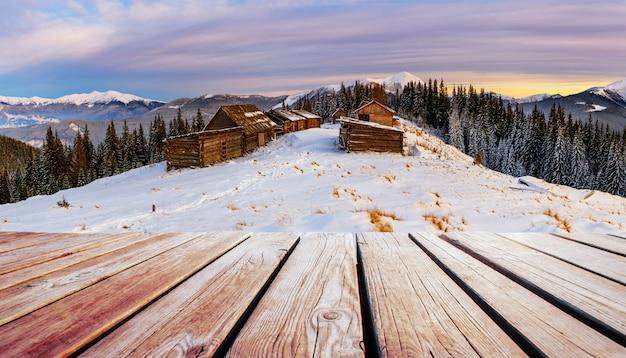 Paisagem de montanhas de inverno com um bosque nevado e uma cabana de madeira e mesa gasto. Foto Premium