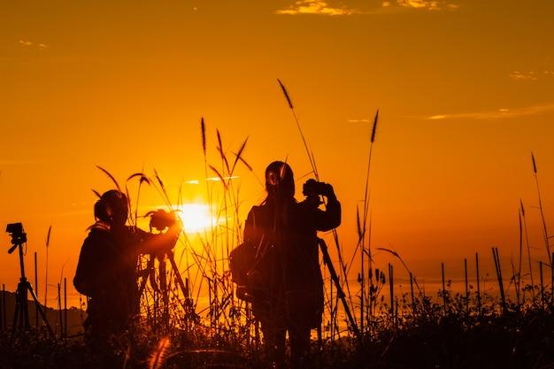 Paisagem de silhueta no turista de tempo de manhã tirar fotos do nascer do sol e névoa na montanha Foto Premium