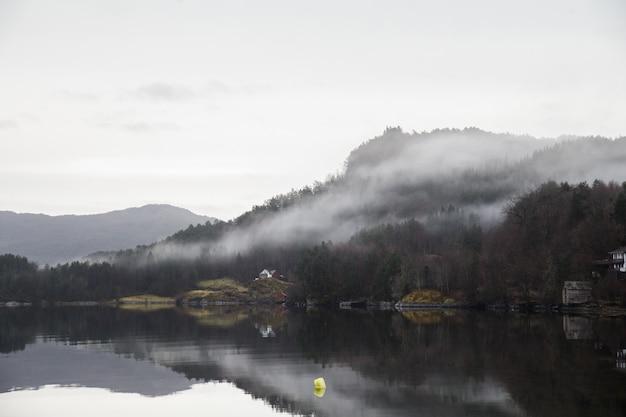 Paisagem de um lago cercado por montanhas cobertas de florestas e neblina, refletindo na água Foto gratuita
