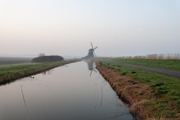 Paisagem de um lago no meio do campo coberto de névoa na holanda Foto gratuita