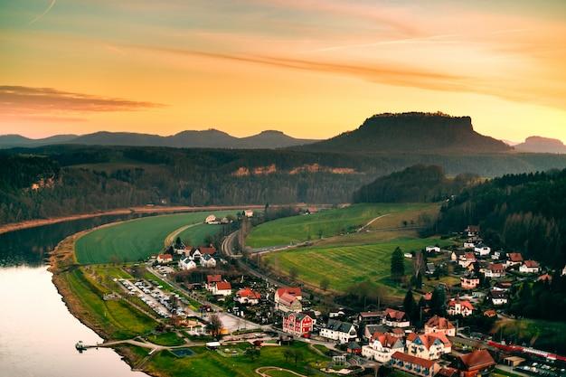 Paisagem de uma altura de uma vila alemã nas montanhas com vista para o rio e as colinas ao pôr do sol Foto Premium