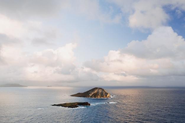 Paisagem de uma pequena ilha rodeada pelo mar sob um céu nublado e luz do sol Foto gratuita