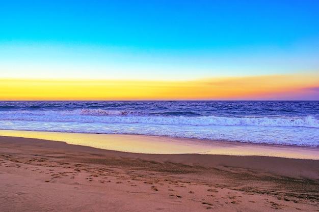 Paisagem de uma praia cercada pelas ondas do mar durante um pôr do sol alaranjado à noite Foto gratuita