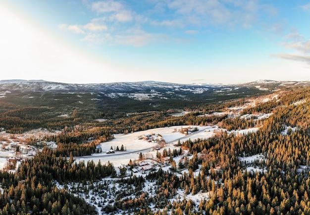 Paisagem de uma vila cercada por florestas cobertas de neve sob um céu azul e luz solar Foto gratuita