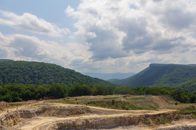 Paisagem de verão com pedreira de calcário contra montanhas e céu nublado Foto Premium