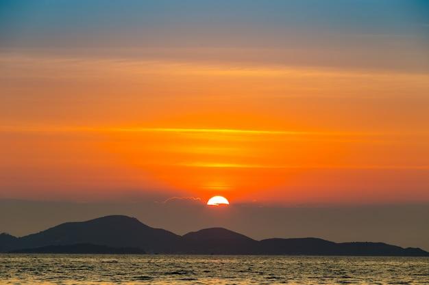 Paisagem do mar com pôr do sol por trás da montanha e mar Foto Premium