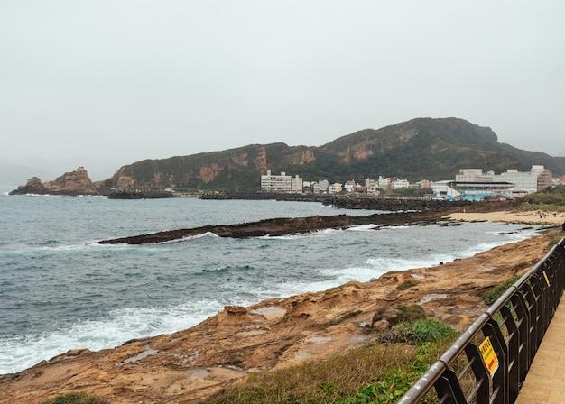Paisagem do yehliu geopark, um cabo na costa norte de taiwan. uma paisagem do mar com edifícios da cidade Foto Premium