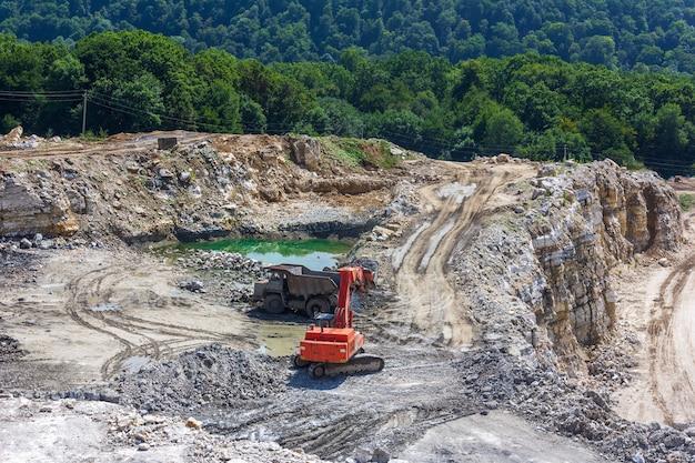 Paisagem industrial com uma escavadeira e um grande caminhão trabalhando em uma pedreira de gesso no verão Foto Premium
