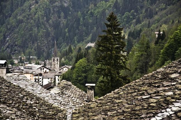 Paisagem montanhosa verde com as casas antigas em primeiro plano Foto gratuita