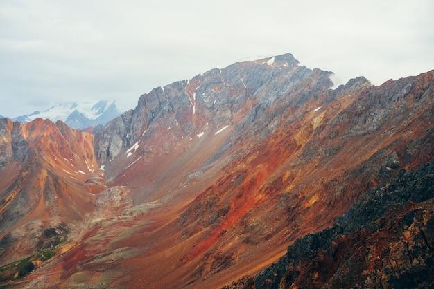 Paisagem multicolor vívida ao cume da grande montanha rochosa. close-up áspero da parede das montanhas gigantes. rochas e pedras vermelhas do amarelo alaranjado. belas paisagens das montanhas rochosas coloridas. cordilheira multicolorida. Foto Premium
