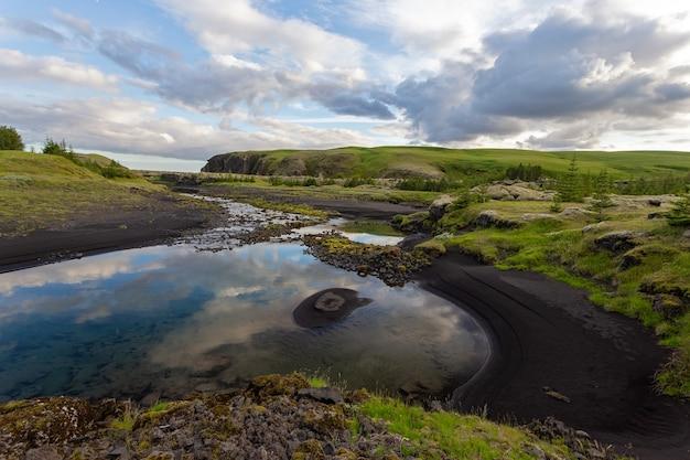 Paisagem natural de verão com areia preta na margem de um rio e nuvens no céu, islândia, europa Foto Premium