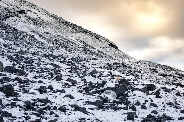 Paisagem rochosa das montanhas nevadas sob um céu nublado durante o dia Foto gratuita