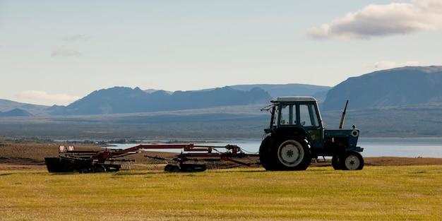 Paisagem, trator, puxando máquinas agrícolas antes da montanha acidentada Foto Premium