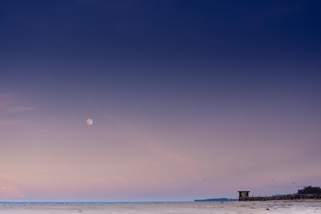 Paisagem, vista do mar praia de areia branca a atmosfera à noite, pôr do sol, pode ver a lua claramente. Foto Premium