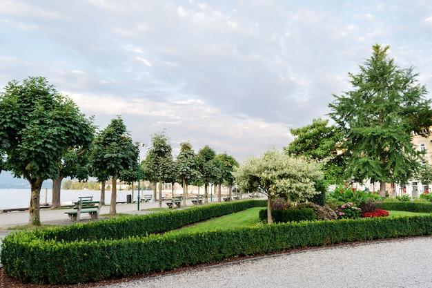 Paisagismo do aterro da cidade com árvores aparadas, arbustos e canteiros de flores. Foto Premium