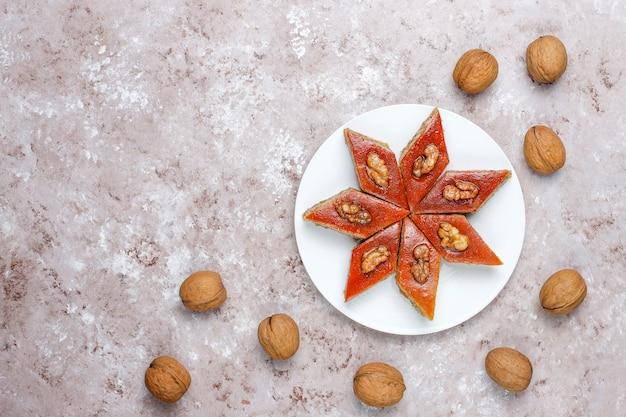 Pakhlava nacional de pastelaria do azerbaijão na chapa branca, vista superior, feriado de novruz da celebração do ano novo da mola. Foto gratuita