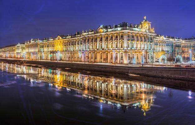 Palácio de inverno em são petersburgo e seu reflexo no neva em uma noite de inverno Foto Premium