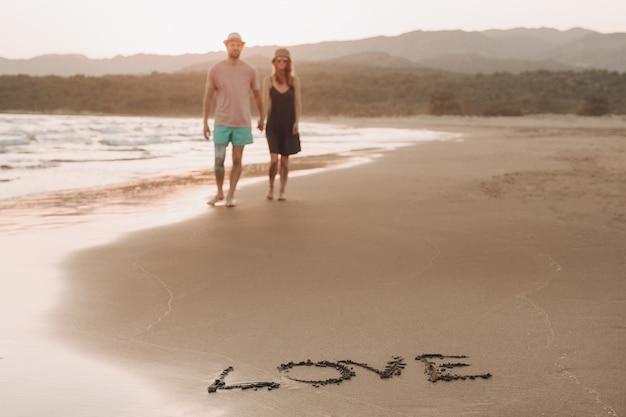 Palavra amor na costa de areia e turva casal apaixonado no fundo andando Foto gratuita