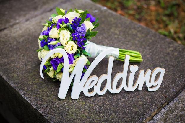Palavra casamento e bouquet de noiva deitado na calçada Foto Premium