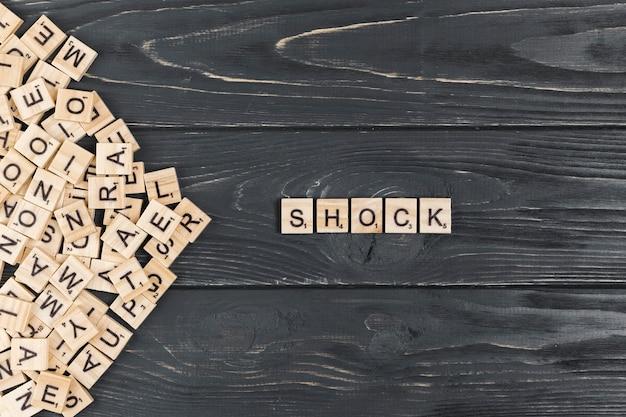 Palavra de choque em fundo de madeira Foto gratuita