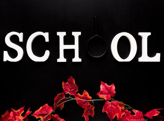 Palavra de escola branca acima ramo de hera vermelha em fundo preto Foto gratuita