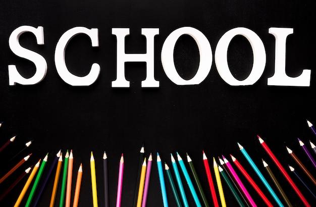 Palavra de escola e lápis de cor sobre fundo preto Foto gratuita