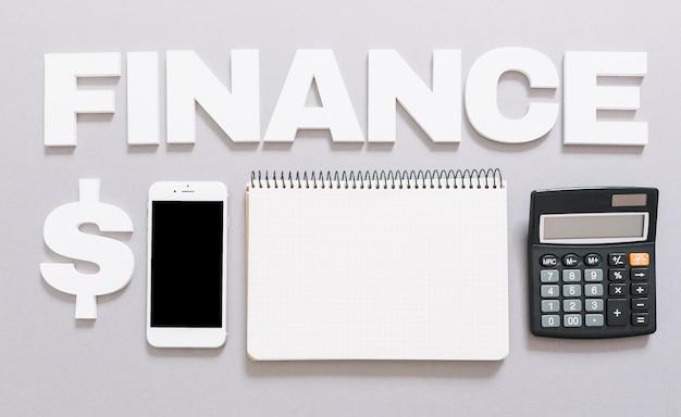 Palavra de finanças com cifrão; celular; caderno espiral e calculadora em fundo cinza Foto gratuita