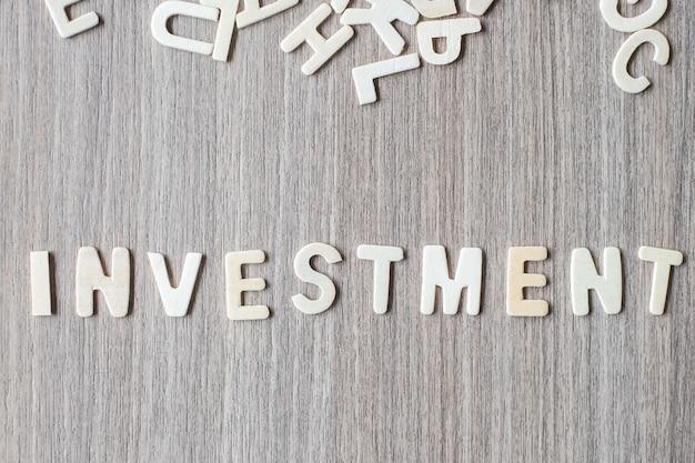 Palavra de investimento de letras do alfabeto de madeira. conceito de negócio e idéia Foto Premium