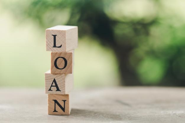 Palavra de madeira empréstimo em pé na mesa de madeira, usando como conceito de negócio de fundo Foto Premium