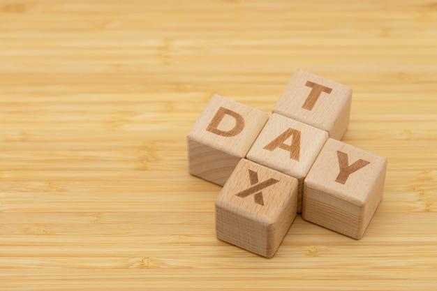 Palavra de madeira imposto dia permanente na mesa de madeira, usando como conceito de negócio de fundo Foto Premium