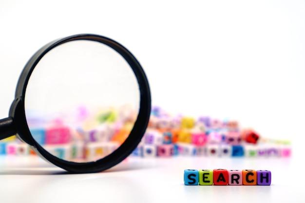 Palavra de pesquisa com a lupa em grânulos de letra do alfabeto Foto Premium