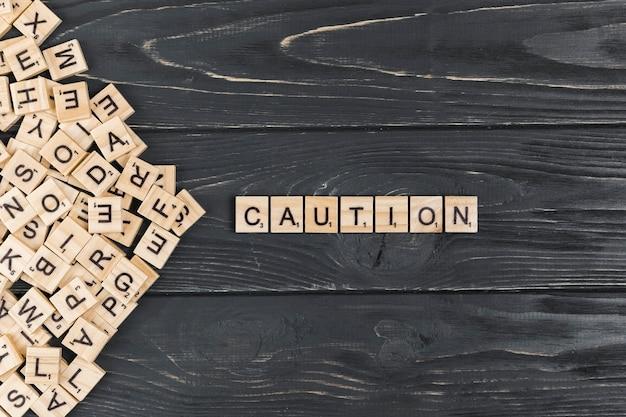 Palavra de precaução no fundo de madeira Foto gratuita