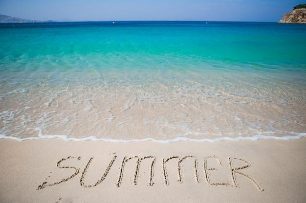 Palavra de verão manuscrita na praia com ondas suaves do oceano no fundo Foto Premium