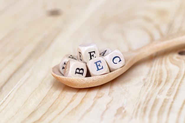 Palavra de vitamina vista superior feita de letras de madeira sobre a mesa e abcde na colher de madeira Foto Premium