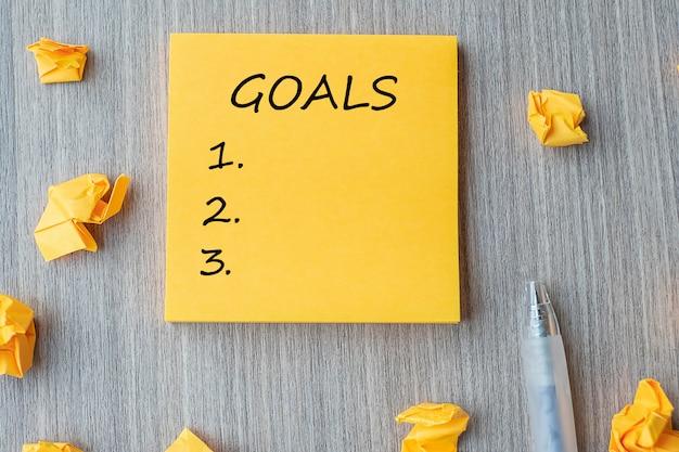 Palavra do objetivo na nota amarela com papel desintegrado em madeira Foto Premium