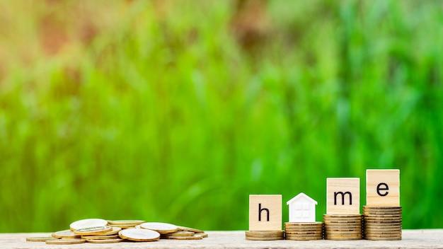 Palavra em casa na pilha de moedas e uma pilha de moedas de ouro na mesa de madeira Foto Premium