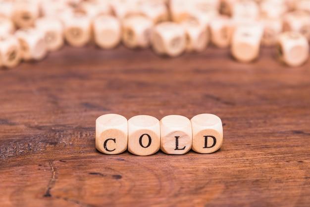 Palavra fria organizada com dadinhos de madeira Foto gratuita