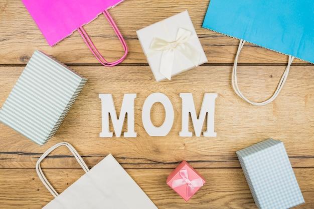 Palavra mãe entre caixas de presentes e pacotes de papel Foto gratuita