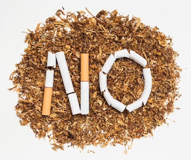 Palavra não feita de cigarro quebrado sobre tabaco Foto gratuita