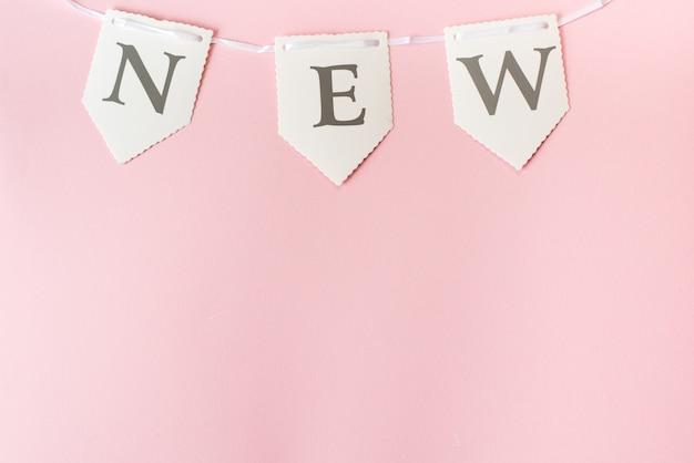 Palavra nova no fundo rosa pastel, vista superior com espaço de cópia Foto Premium