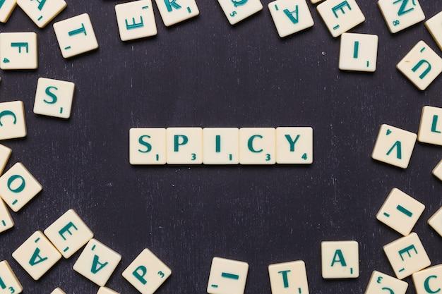 Palavra picante em letras scrabble sobre pano de fundo preto Foto gratuita